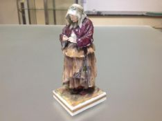 A 19th century Continental porcelain figure of a beggar worman, in Naples style, modelled in
