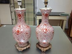 A pair of porcelain baluster vasiform table lamps, each decorated in the Chinese taste with coral