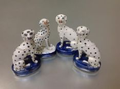 A group of five Staffordshire models of seated dalmatians, each on an oval blue base with gilt chain