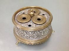 An Indian brass and silvered brass inkstand, circular, fitted with three inkwells and three pen