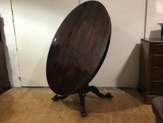 An early Victorian rosewood tilt-top breakfast table, c. 1840, the oval top with moulded edge and