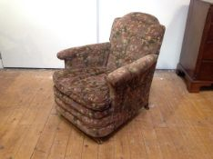A small 1920's club chair, with arched upholstered back above a loose-cushioned seat between