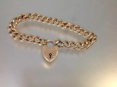 A gold curblink bracelet with a heart padlock clasp, the clasp stamped 15ct. Length c. 21cm, 21