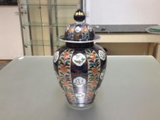 A Japanese Imari porcelain baluster jar and cover, the domed cover and body decorated in panels