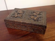 A Chinese camphor-lined carved wooden cigarette box, c. 1900, of rectangular form, the cover and