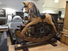 An Ian Armstrong rocking horse of laminated sectioned pine, complete with leather saddle, with
