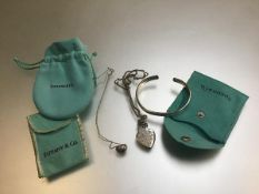 A silver adjustable bangle, Please Return To pendant on trace link chain and a bean pendant on