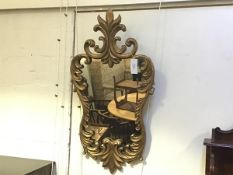 A giltwood rococo style mirror, the cartouche within a conforming frame boldly carved with scrolling