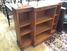 A reproduction yew wood breakfront bookcase, the crossbanded top above a centre open shelf