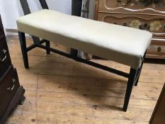 An ebonised duet piano stool with upholstered top and square tapered supports (52cm x 105cm x 38cm)