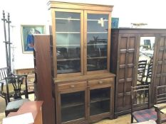 An Edwardian oak two part cabinet bookcase, the moulded cornice above a pair of glazed panel doors