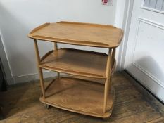 An Ercol light elm three tier trolley with moulded edges, raised on turned supports, complete with