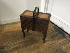A mahogany concertina sewing box with centre handle enclosing a fitted interior, on carved moulded