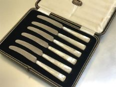 A set of six stainless steel mother of pearl handled side knives