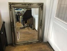 A modern silvered rococo style frame wall mirror with bevelled glass plate (118cm x 85cm)