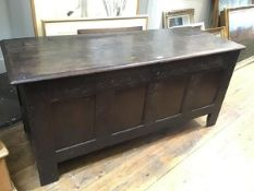 A late 17thc/early 18thc oak four panel coffer, the plain rectangular cover with moulded edge over