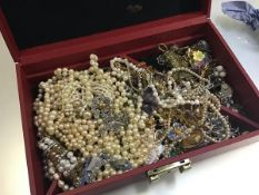 A box containing a large collection of paste pearl necklaces, bracelets, gilt metal chains,