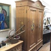 A late 19thc Swiss pine armoire, the arched moulded top above a painted fruit and floral frieze,
