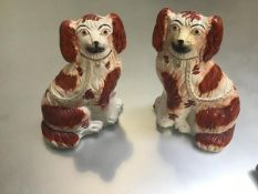 A pair of 19thc Staffordshire pottery chimney spaniels decorated with polychrome enamels (h.24cm x
