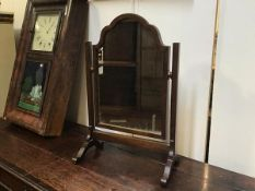 An oak frame swing mirror with arched top on square section supports (h.62cm x 40cm)