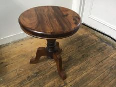 An Eastern hardwood circular top occasional table, the top with moulded edge raised on turned column
