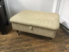 An upholstered ottoman stool in herringbone fabric with lift up top enclosing a black baize lined