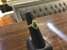 A 14ct gold ring set marquise shaped jadeite green panel mounted with leaf scrolling shoulders (