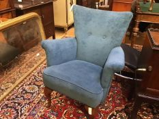 A 1950s tub chair with button back, upholstered arms and stuffover seat, in blue plush, raised on