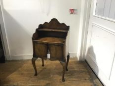 A figured walnut bedside with scalloped top and open shelf above two panel doors, raised on carved