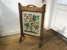 An Arts & Crafts oak firescreen with arched centre handle to top enclosing a glazed crewel work