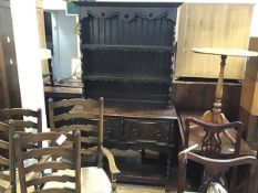 A 1920s oak dresser, the moulded cornice above two open shelves, above two frieze drawers, with