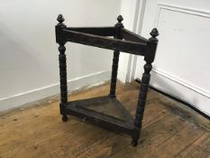 A 1930s oak carved corner stick stand with arcaded frieze raised on bobbin turned supports