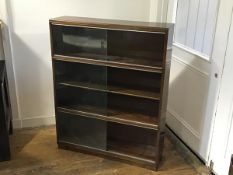 A modern three section mahogany upright sectional style bookcase fitted three pairs of sliding