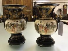 A pair of Japanese Satsuma pottery vases, Meiji period, c. 1900, of twin-handled baluster form,