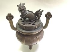 A Chinese bronze censer, of circular bellied form, the cover mounted with a kylin finial, the body