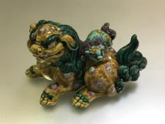 A Chinese biscuit model of a recumbent Buddhist lion dog, the vessel with cover modelled as it's