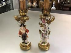 A pair of German porcelain figural table lamps, probably Volkstedt, c. 1920, modelled as a lady