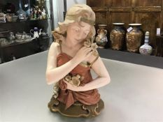 An Austrian pottery half figure of a girl, Ernst Wahliss Vienna, c. 1900, in the Art Nouveau