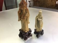 A Chinese soapstone carving of an Immortal, portrayed with scroll and pen, on an integral rock-