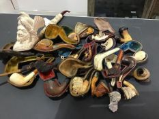 A large collection of Meerscham and other character pipes, some cased, some with silver mounts,