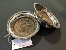 A pair of Sheffield plate wine coasters or bottle slides with turned wooden bases d.12cm