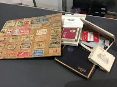 A collection of match boxes mounted on a wooden board together with a collection of used cigarette