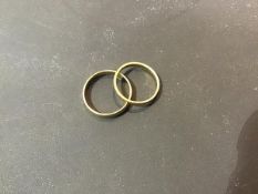 An 18ct gold wedding band (3g), together with a unmarked yellow metal wedding band (1.8g) (2)