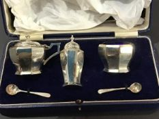 A cased three piece Mappin & Webb Birmingham silver condiment set, with blue glass liners,