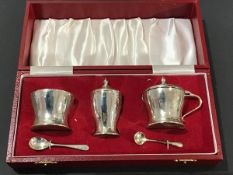 A cased three piece Birmingham silver condiment set, with blue glass liners and spoons
