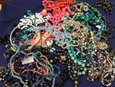 A mixed lot of beads and necklaces including glass, hardstone, mother of pearl, some with white