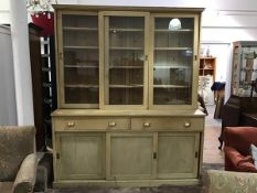 A pine two part Estate kitchen dresser c.1900, the moulded top above three glazed sliding doors,