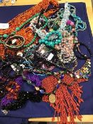 A mixed lot of necklaces including a multi strand bead necklace, a coral style choker, a polished