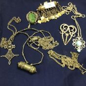 A mixed lot of white metal and metal Eastern jewellery including brooches, pendants, chains, jade