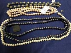 A collection of cultured pearls necklaces, including a long strand of black/silver pearls, green